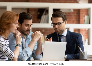 Caucasian male real estate agent or broker consult couple clients show project on laptop screen. Man realtor or financial advisor talk have consultation with spouses at office meeting. Rental concept.