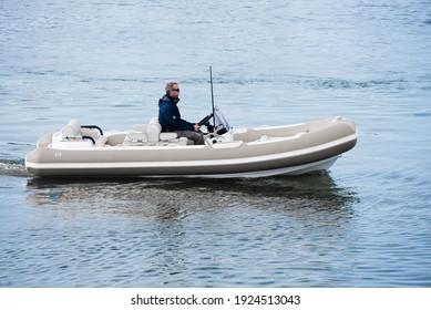 Caucasian Male Superyacht Deckhand doing tender driving on turbo jet boat in port