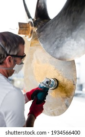 Caucasian male superyacht deckhand engineer polishing a yacht propeller with a power tool, gloves, mask and eye protection glasses