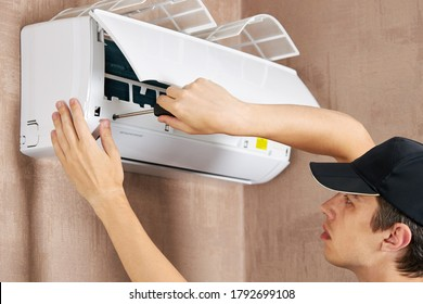 caucasian male technician service worker repairing air conditioner. diy concept.