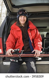 Caucasian male teenager sitting on back of SUV holding skis.