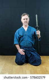 Caucasian male training Japanese sport, iaido. Sitting on floor holding a Japanese sword looking at camera. Indoor shot.