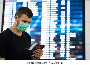 Caucasian male traveler with medical face mask in airport. Man wearing a protective mask against coronavirus. Facial hygienic mask for safety outdoor. Environmental awareness or virus spread concept.
