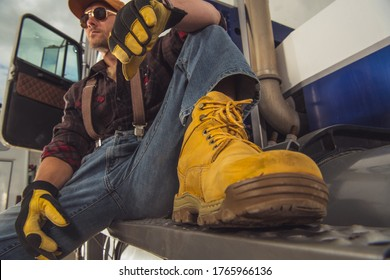 Caucasian Male Trucker Sitting Outide Of His Vehicle And Relaxing During Break.