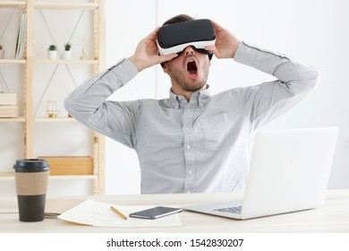 Caucasian male with VR headset one feeling amazed with virtual reality experience while spending break in office