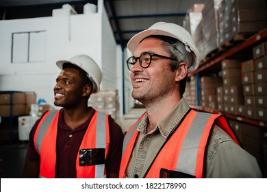 caucasian male worker wearing spectacles laughing with mixed race worker standing in factory warehouse.