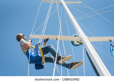 Caucasian Male working up the mast of a sailing yacht, with rope and bosun's chair on a sunny day with blue sky