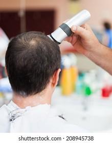 Caucasian man in a barber shop getting a very short haircut