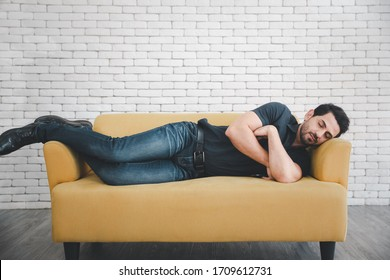caucasian man with beard napping on yellow sofa with smart phone in hand