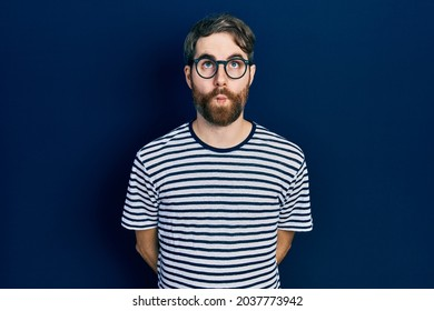 Caucasian man with beard wearing striped t shirt and glasses making fish face with lips, crazy and comical gesture. funny expression.
