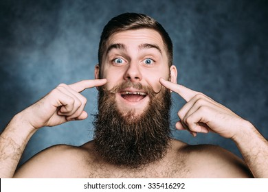 Caucasian man with big beard point the fingers his funny spinning mustache and smile. Horizontal