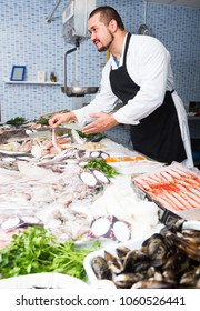 caucasian man in black apron and white cover-slut behind counter holding fish