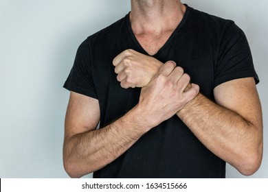 Caucasian man with black t-shirt with hand on his wrist, expression of pain