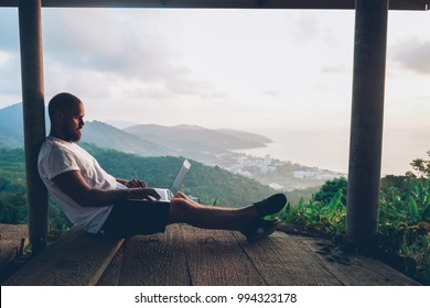 Caucasian man blogger relaxing outdoors while working on freelance against beautiful Asian landscape with jungles. Guy traveler typing text on netbook using internet connection on portable usb modem