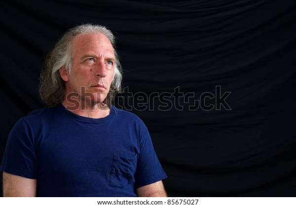 A caucasian man with blue eyes and long white hair is looking up against black background.