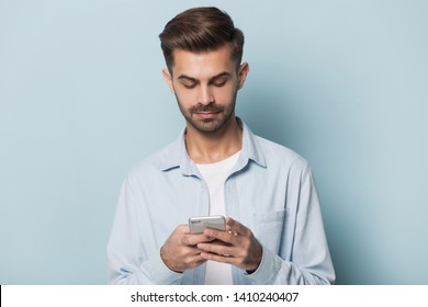 Caucasian man in casual clothes stand isolated on blue studio background using smartphone look at screen texting message, millennial guy social network user hold cell phone gadget check media concept