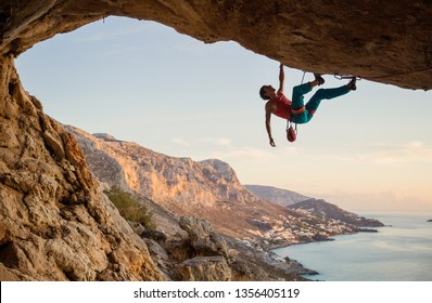 Caucasian man climbing challenging route in cave at sunset
