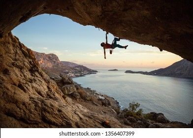 Caucasian man climbing challenging route in cave, against beautiful evening view