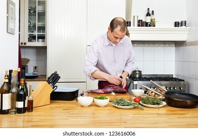 Caucasian man cutting meat on chopping board at kitchen counter