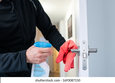 Caucasian man disinfecting the handle of a hotel door with a pink cloth and disinfectant cleaning product.