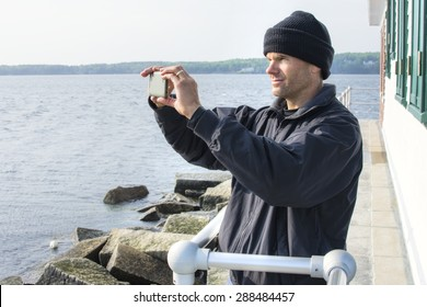 Caucasian man dressed in black jacket and beanie takes cell phone photo of scenic view of bay at the lighthouse at end of breakwater in Rockland, Maine