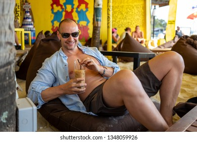 Caucasian man with drink relaxes at Langkawi beach bar