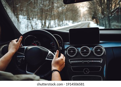 Caucasian man driving car on the empty road, winter and snow background