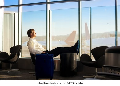 Caucasian man in early fifties, side profile,  sleeping with legs up in airport terminal, airplanes in background on tarmac