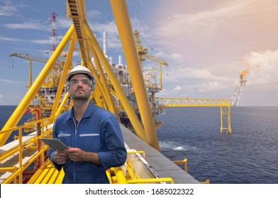 Caucasian man engineer staff worker with tablet in hand and offshore rig background concept.