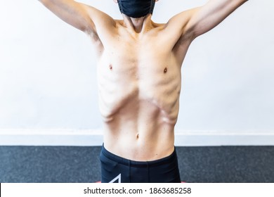 caucasian man with a face mask training hypopressive abdominal exercises on the mat