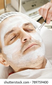 Caucasian man face under cosmetic mask getting made by cosmetologist hand with brush. Closeup Vertical shot