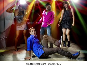 Caucasian man falls but confidently plays cool in a dance club
