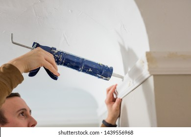 Caucasian man finishes crown moulding installation with caulk sealant