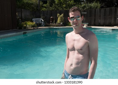 Caucasian man fitness model standing in a  swimming pool  wearing aviator sunglasses and blue swimming suit. Sexy athletic man with defined abs in an outdoor swimming pool in the summer.