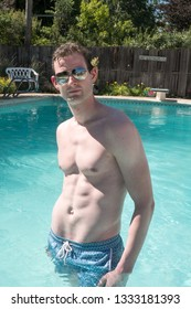 Caucasian man fitness model standing in a  swimming pool looking at the camera wearing aviator sunglasses. Cute athletic guy with defined abs in a swimming pool in the summer.