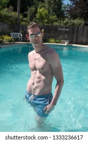 Caucasian man fitness model standing in a  swimming pool  wearing aviator sunglasses and blue swimming suit. Cute athletic boy with defined abs in an outdoor swimming pool in the summer.