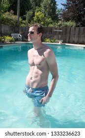 Caucasian man fitness model standing in a  swimming pool wearing aviator sunglasses. Cute athletic guy with defined abs in a swimming pool in the summer water to waist.