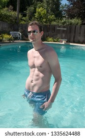 Caucasian man fitness model standing in a  swimming pool looking at the camera wearing aviator sunglasses and blue swimming suit. Cute athletic guy with defined abs in a swimming pool in the summer