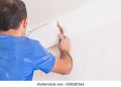 Caucasian man fixes ceiling skirting.