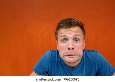 Caucasian man with funny face on red background. Concept of unexpected news
