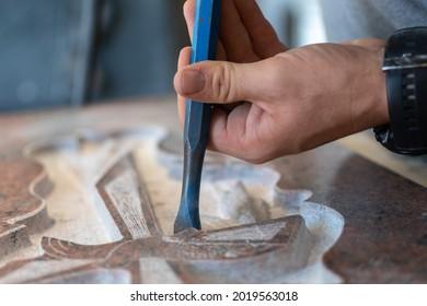caucasian man hands bushhammered a tombstone in a workshop, work concept
