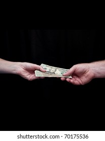 Caucasian man hands his wife one hundred dollars in U.S. currency. Twenty dollar bills. Against a black background. Hands and wrists only.