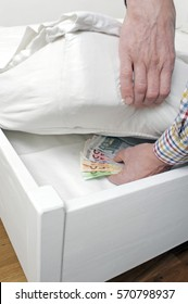 Caucasian man is hiding euro banknotes under his mattress