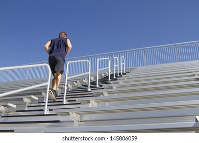 A Caucasian man in his twenties works out at a stadium.
