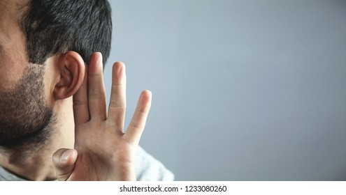 Caucasian man hold hand near ear. Trying to hear a gossip