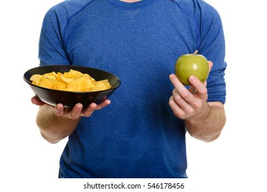 Caucasian man holding bowl of potato chips and green apple isolated against white background