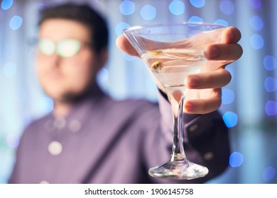 Caucasian man holding glass of martini with olive on background