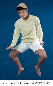 hombre caucásico saltando aislado con camisa amarilla y gorra de fondo azul