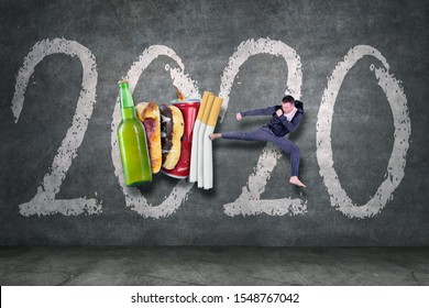 Caucasian man kicking drink and fast food with number 2020 in the studio. Healthy lifestyle resolution concept