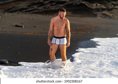 Caucasian man looking down dressing underwear on the beach. El Golfo, Lanzarote, Canary Islands